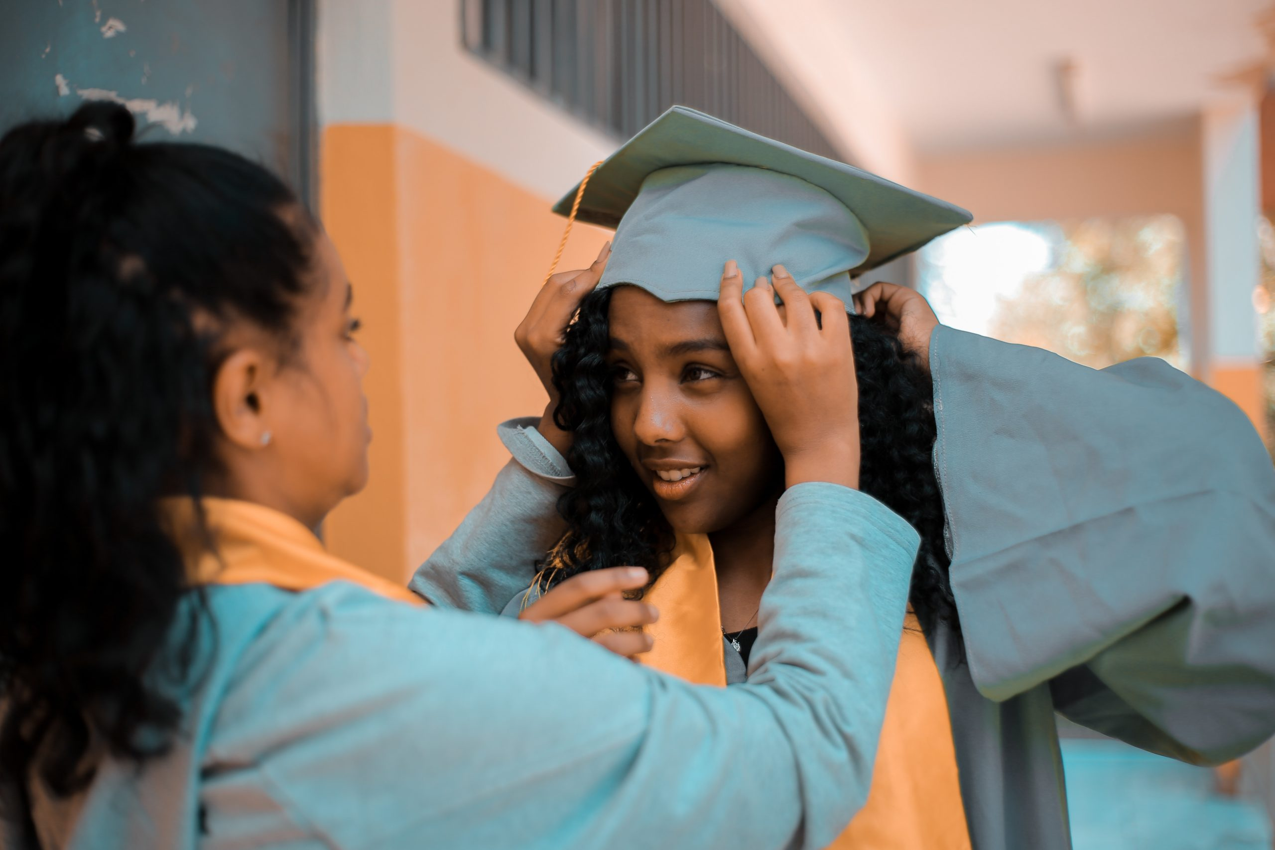 two girls adjusting graduation cap who will soon be part of a company's campus hiring strategy