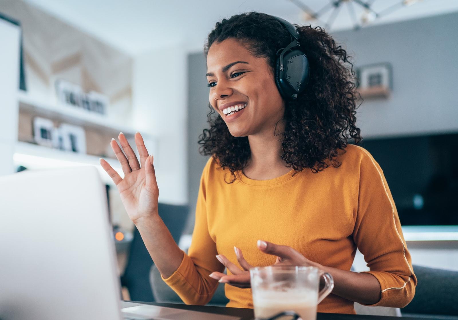Smiling woman waving at laptop screen